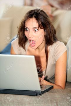 7577473-woman-with-surprised-look-in-front-of-computer-stock-photo-shocked